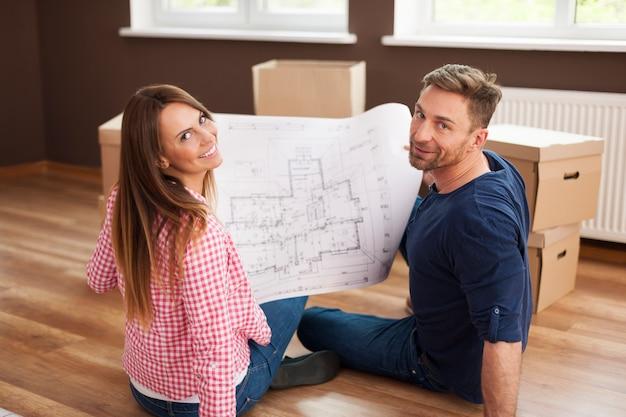 Pareja feliz en apartamento nuevo con plano