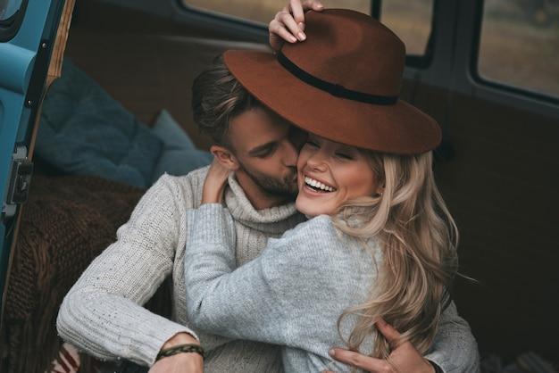 Pareja feliz. apuesto joven besando a su atractiva novia y sonriendo mientras está sentado en una mini furgoneta de estilo retro azul