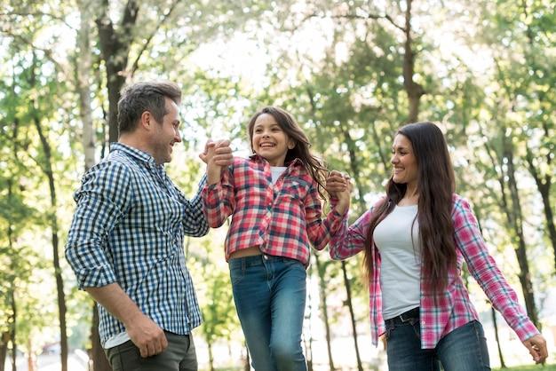 Pareja feliz balanceando a su hija entre ellos en el parque