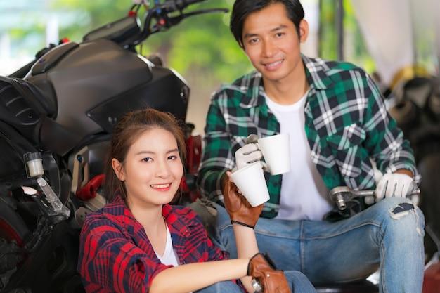 Pareja feliz bebiendo café en un taller de reparación de motocicletas