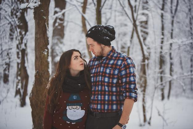 Pareja feliz en el bosque de invierno