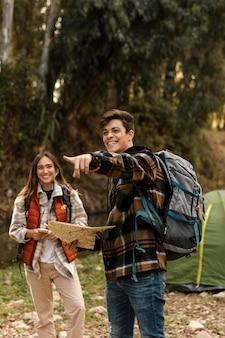 Pareja feliz en el bosque sosteniendo mapa y apuntando