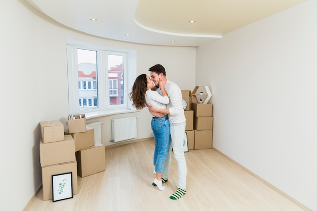 Pareja feliz con cajas de cartón en casa nueva