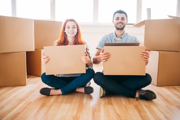Pareja feliz con cajas de cartón en las manos sentadas en el suelo, mudarse a casa nueva, inauguración de la casa