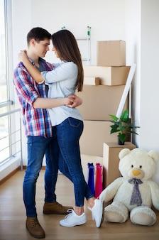Pareja feliz con cajas de mudarse a nueva casa