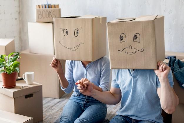 Pareja feliz en casa el día de la mudanza con cajas sobre cabezas