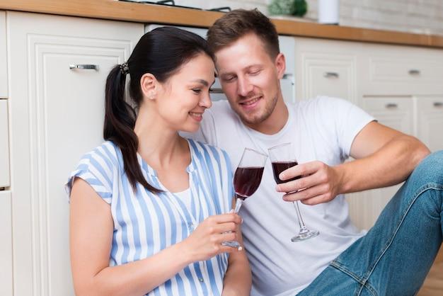 Pareja feliz celebración copas de vino en la cocina