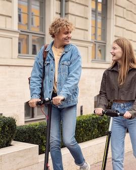 Pareja feliz en la ciudad montando scooters eléctricos