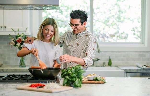 Pareja feliz cocinando en la cocina