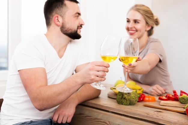 Pareja feliz comiendo verduras y bebiendo juntos