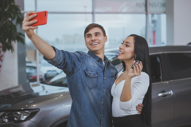 Pareja feliz comprando un auto nuevo en el salón del concesionario