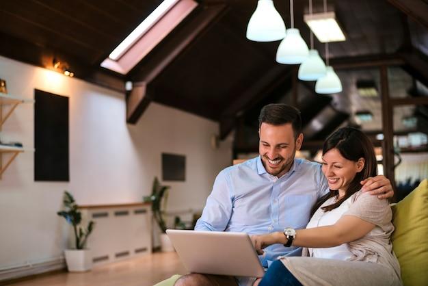 Pareja feliz con la computadora portátil pasar tiempo juntos en casa