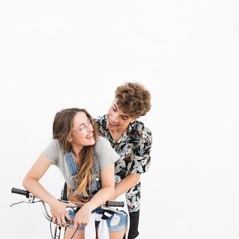 Pareja feliz con bicicleta sobre fondo blanco