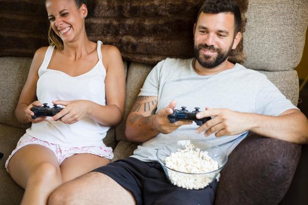 Pareja feliz con palomitas de maíz jugando videojuegos
