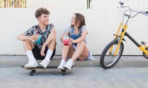 Pareja feliz con patineta beber jugo junto a la bicicleta