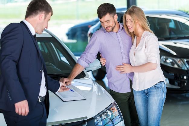 Pareja feliz con concesionario de automóviles en salón del automóvil o salón