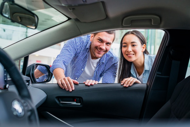 Pareja feliz en concesionario de coches