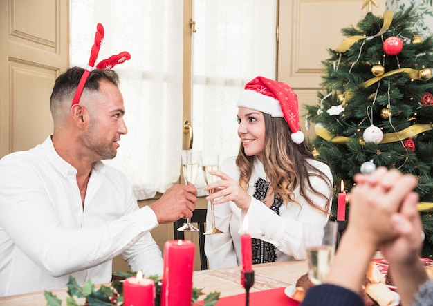 Pareja feliz copas copas en mesa festiva