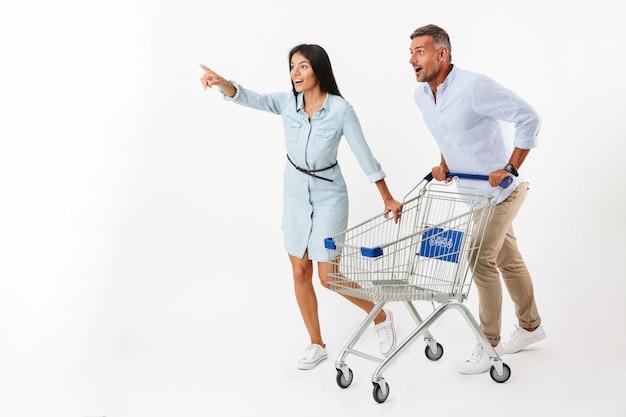 Pareja feliz corriendo con un carrito de compras