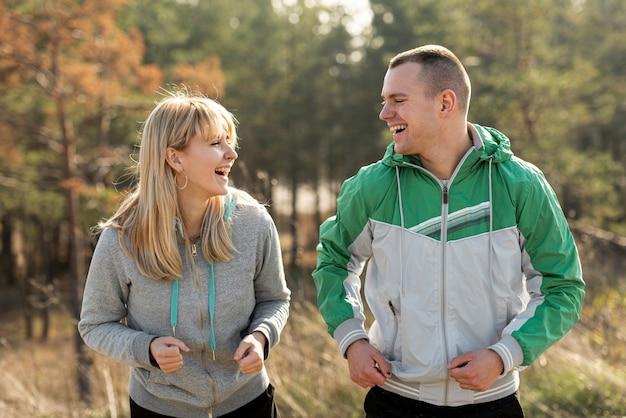 Pareja feliz corriendo juntos en la naturaleza