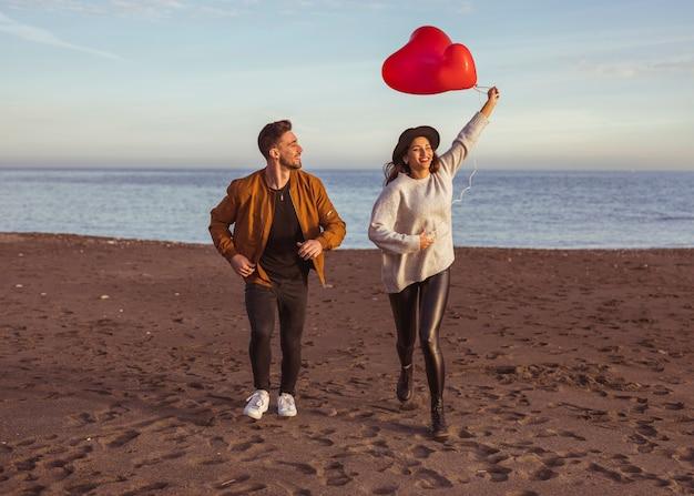 Pareja feliz corriendo en la orilla del mar con globos de corazón