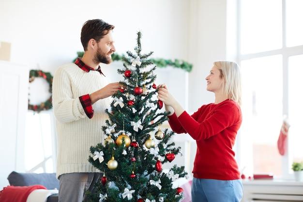 Pareja feliz decorando el árbol de navidad