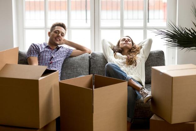 Pareja feliz descansando en el sofá después de mudarse a casa nueva