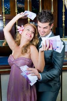Pareja feliz después de ganar mucho dinero en el casino