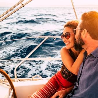 Pareja feliz disfruta de un paseo en velero en yate - relación de amor y estilo de vida romántico con personas adultas en vacaciones de verano vacaciones de viaje - océano y agua azul en el fondo