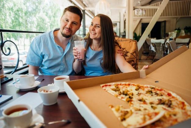 Pareja feliz disfrutando de pizza y batido en café