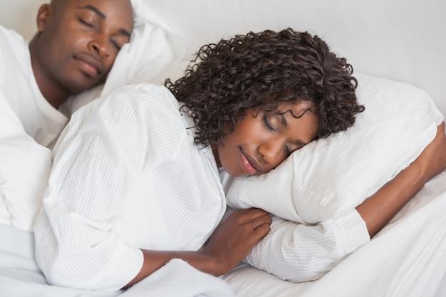 Pareja feliz durmiendo juntos en la cama