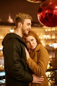 Una pareja feliz se encuentra en un abrazo en la calle por la noche en las luces festivas