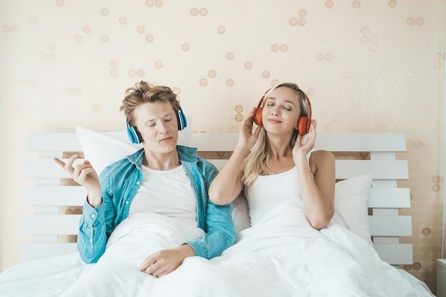 Pareja feliz escuchando la canción en la mañana en el dormitorio
