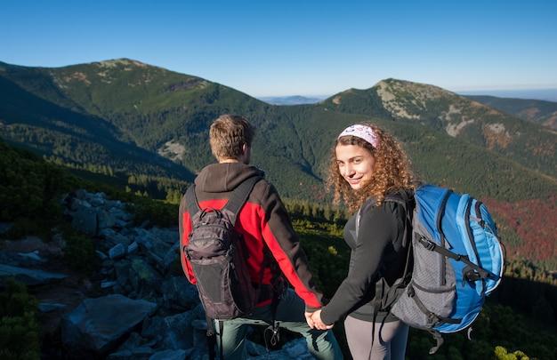 Pareja feliz excursionista caminando en la naturaleza alta en las montañas