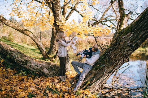 La pareja feliz de la familia con su pequeño niño y perrito en otoño parquea en día soleado.