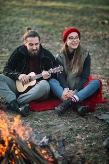 Pareja feliz con guitarra cerca de fogata