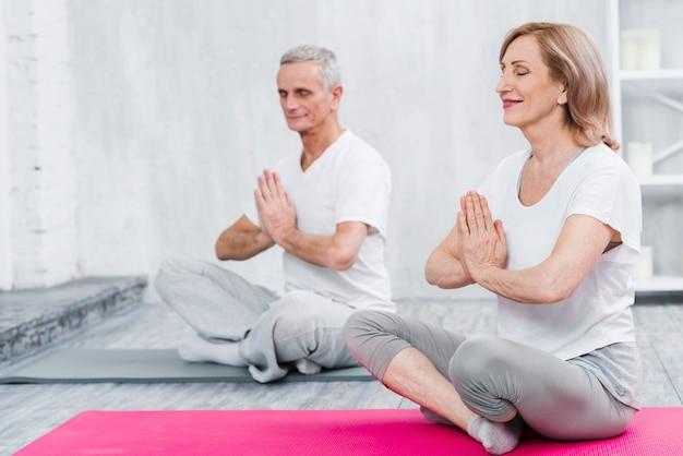 Pareja feliz haciendo meditación en estera de yoga