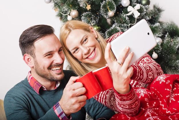 Pareja feliz haciendo un selfie sobre un fondo de árbol de navidad