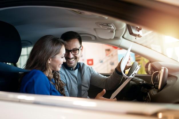 Pareja feliz en el interior del coche en la sala de exposición del concesionario de vehículos.