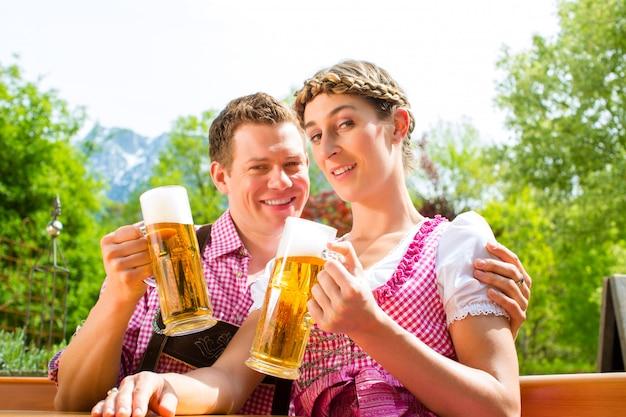 Pareja feliz en el jardín de la cerveza bebiendo cerveza