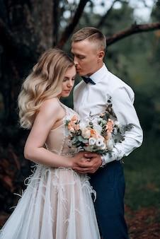 Pareja feliz. joven hermosa novia y el novio con un ramo de novia