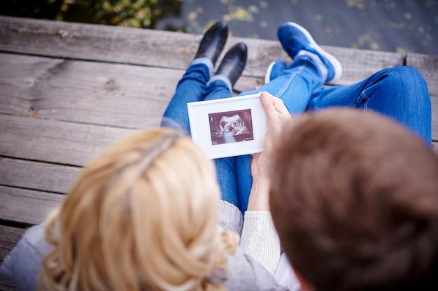 Pareja feliz está llevando a cabo la ecografía de su bebé