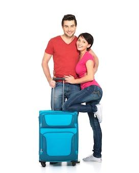 Pareja feliz con maleta va a viajar, de pie en el estudio sobre fondo blanco.