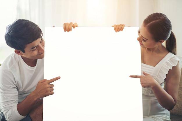 Pareja feliz mano sosteniendo el espacio en blanco blanco