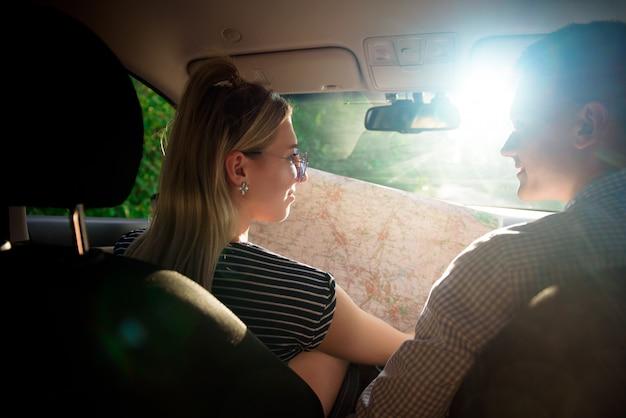 Pareja feliz con mapa en coche