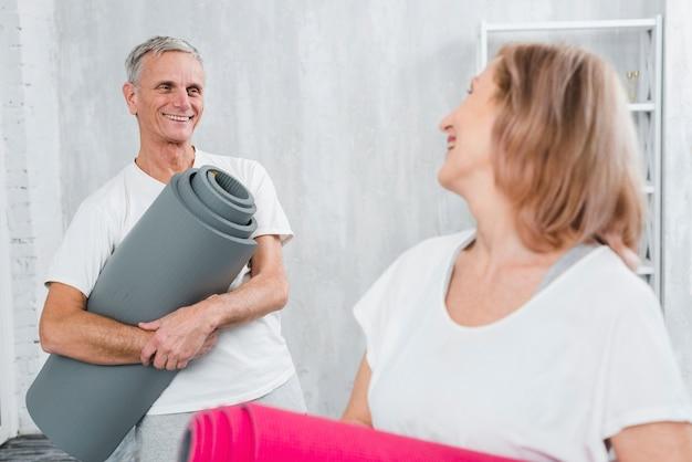 Pareja feliz mirando el uno al otro sosteniendo la estera de yoga