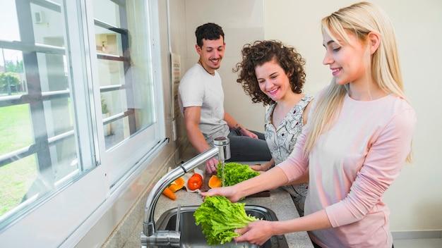 Pareja feliz mirando a una joven amiga lavando la lechuga en el fregadero de la cocina