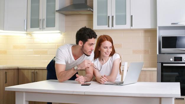 Pareja feliz mirando portátil en casa en la cocina