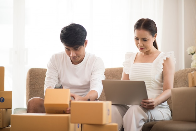 Pareja feliz en la oficina en casa con negocios en línea, mercadeo en línea y trabajo independiente