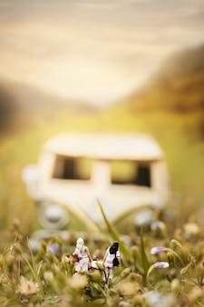 Pareja feliz pasajero con furgoneta miniatura vintage en la naturaleza. concepto de viaje y vacaciones, profundidad de composición de campo.